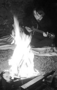 Playing guitar beyond a campfire